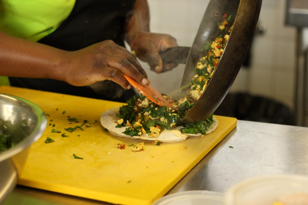 Tofu scramble wrap being assembled at Free Food*