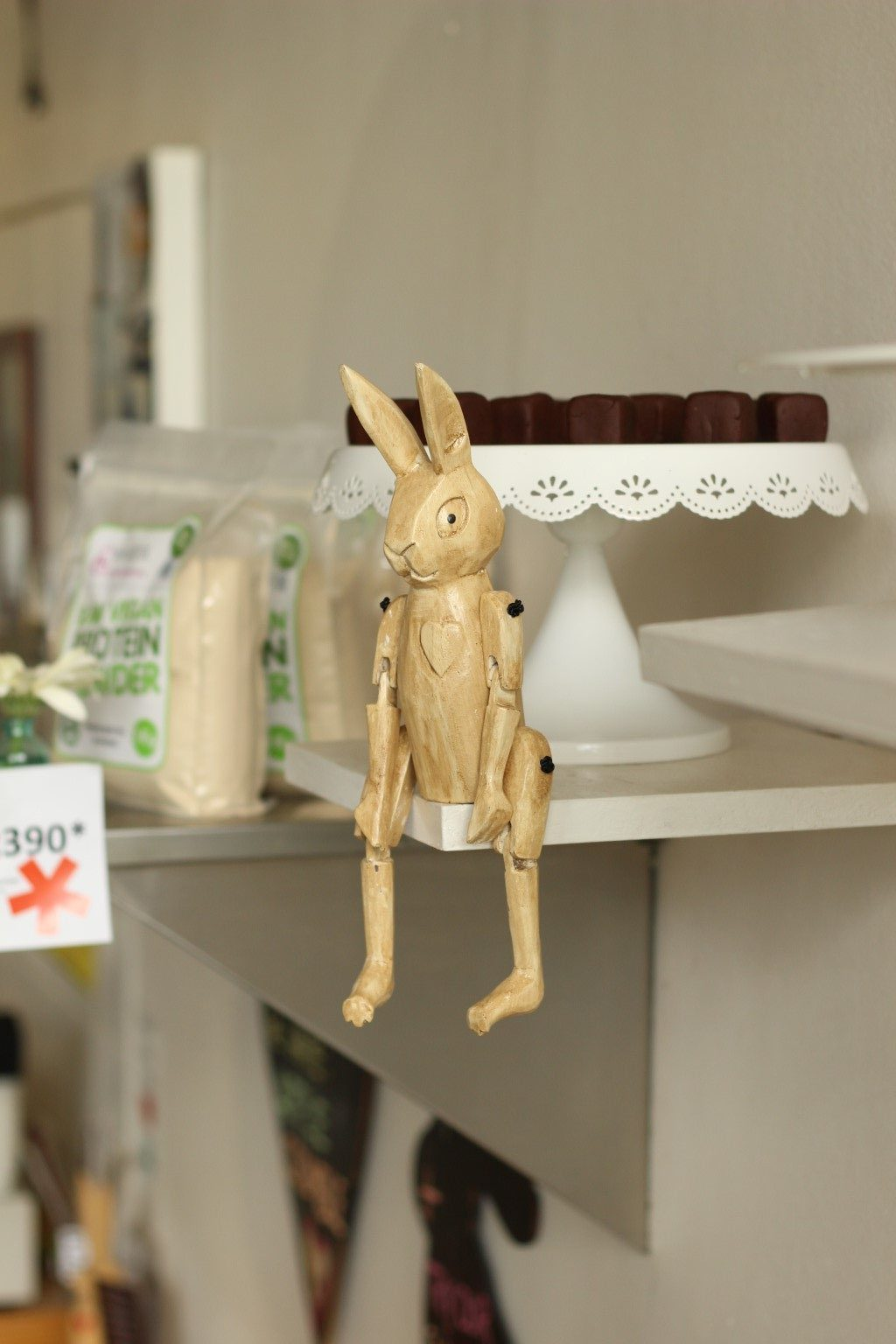 Wooden rabbits decorate the store, this one is guarding some chocolate dice